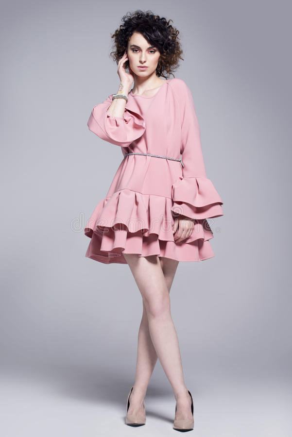 Beautiful young woman in a pink dress with frills stock photo