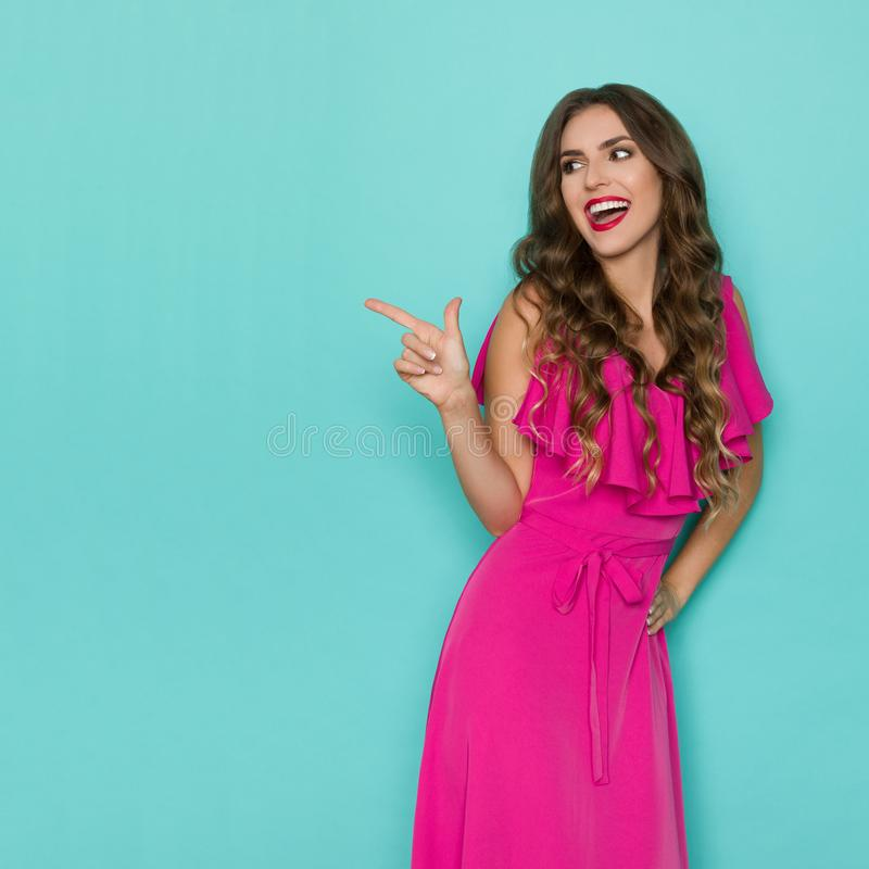 Beautiful Young Woman In Pink Dress Is Pointing, Looking Away And Laughing stock photo