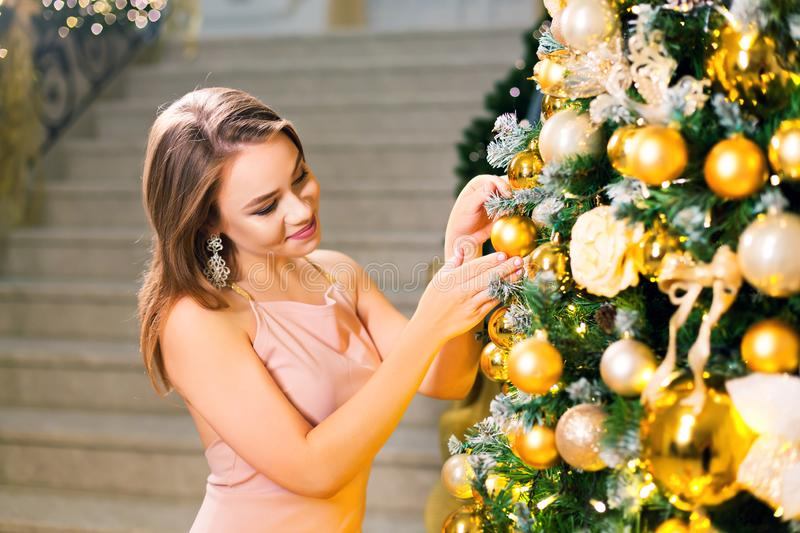 Beautiful young woman in a pink elegant evening dress staying in a chic hall and dressing up a christmas tree with yellow ball on stock image