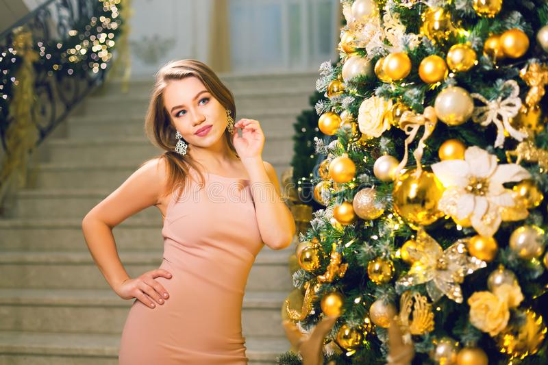 Beautiful young woman in a pink elegant evening dress staying and posing near xmas tree on a new year eve. Beautiful young woman in a pink elegant evening dress royalty free stock photo