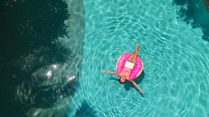 Beautiful young woman with a pink laptop on an inflatable ring in the water in the swimming pool. freelancing, business stock photo