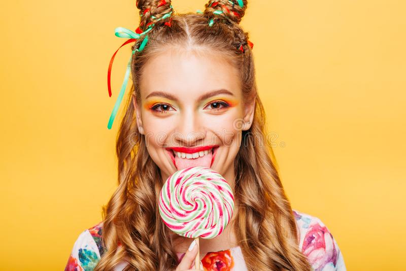 Woman with playful look lick candy with tongue royalty free stock photography