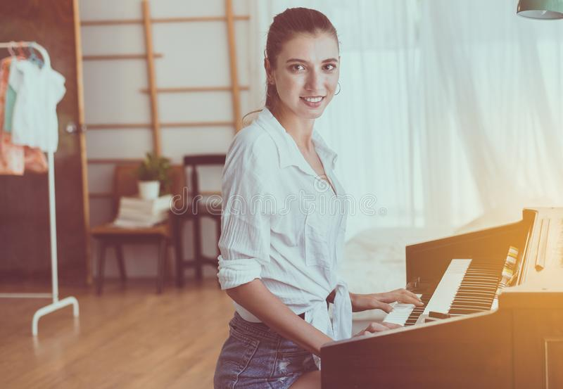 Beautiful young woman playing electronic piano,Happy and smiling,Relaxing time royalty free stock images