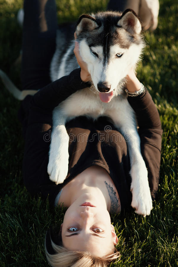 Beautiful young woman playing with funny husky dog outdoors in park at sunny day stock image