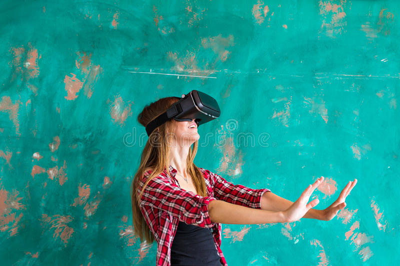 Beautiful young woman playing game in virtual reality glasses stock image