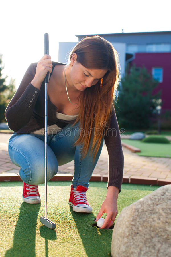 Beautiful young woman playing golf stock images