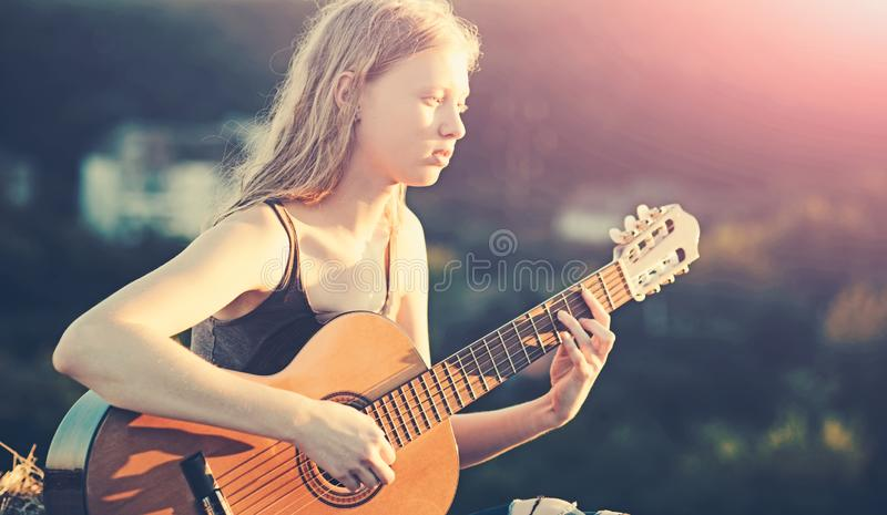 Beautiful young woman playing guitar at sunset, fashion lifestyle stock photography
