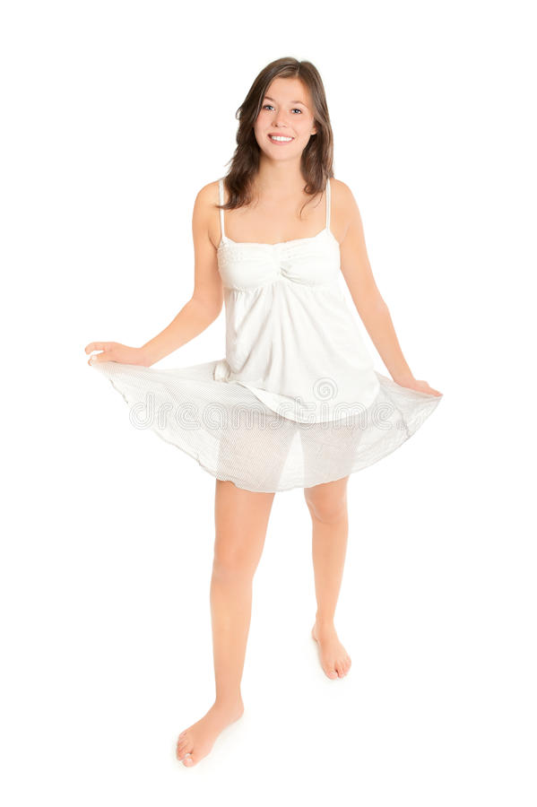 Beautiful young woman playing with her skirt. Full length fashion portrait of a beautiful young woman playing with her short skirt in front of white background stock photo