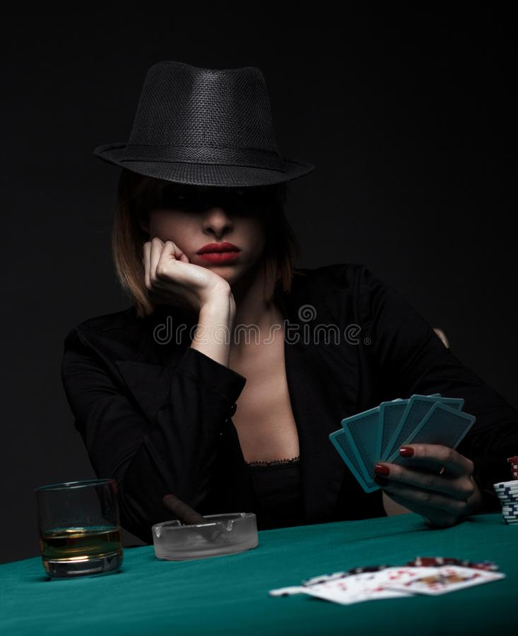 Beautiful young woman playing poker on black background. Beautiful young woman playing poker on isolated black background royalty free stock photography