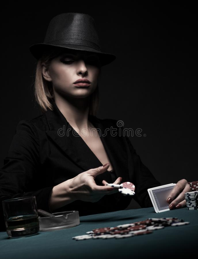 Beautiful young woman playing poker on black background. Beautiful young woman playing poker on isolated black background stock photo