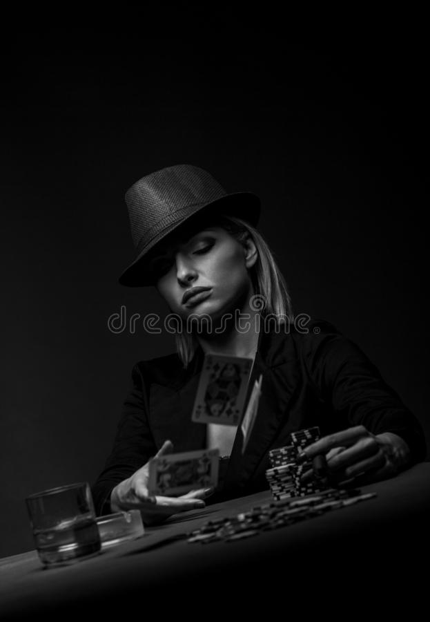 Beautiful young woman playing poker on black background. Beautiful young woman playing poker on isolated black background stock images