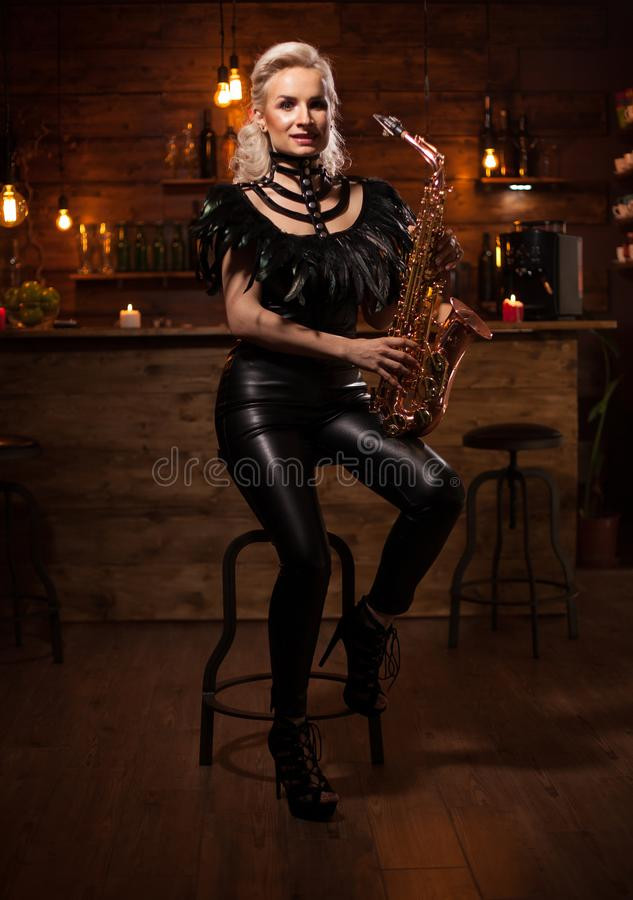 Beautiful young woman playing on saxophone in a vintage pub royalty free stock photo