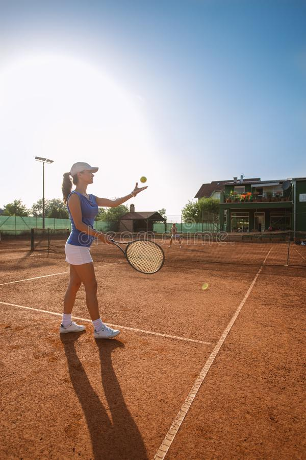 Beautiful young woman playing tennis and serving royalty free stock image