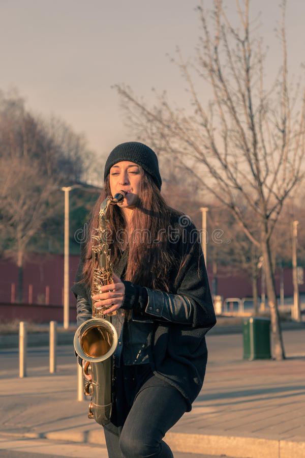 Beautiful young woman playing tenor saxophone. In the city streets royalty free stock photos