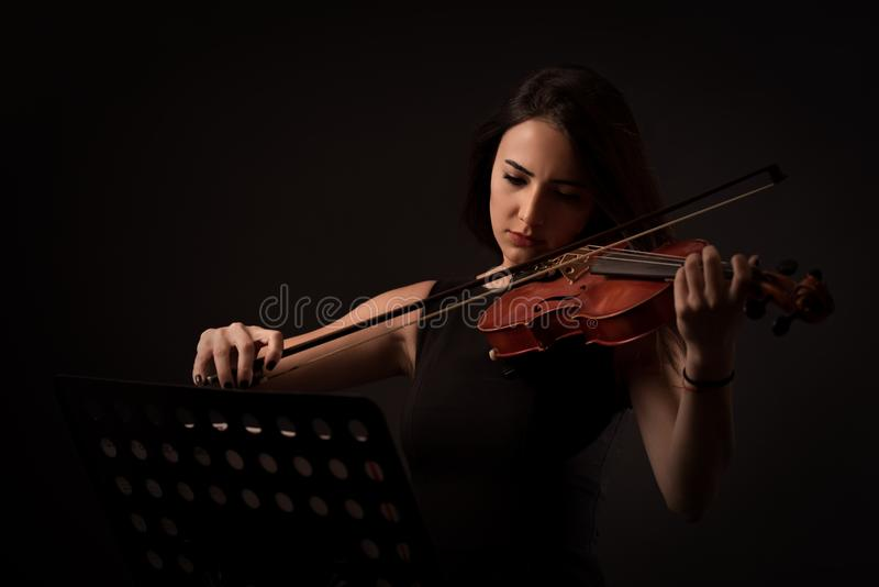 Beautiful young woman playing a violin over black background royalty free stock image