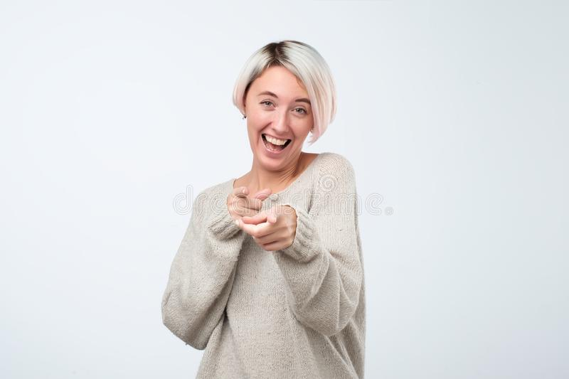Beautiful young woman points with finger and scoffs, short haircut, studio photo. Beautiful young woman points with finger and scoffs, short haircut stock photos