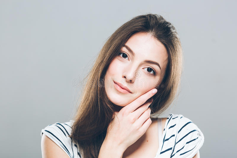 Beautiful young woman portrait cute tender pure smiling touching her chin by fingers attractive gray background royalty free stock images