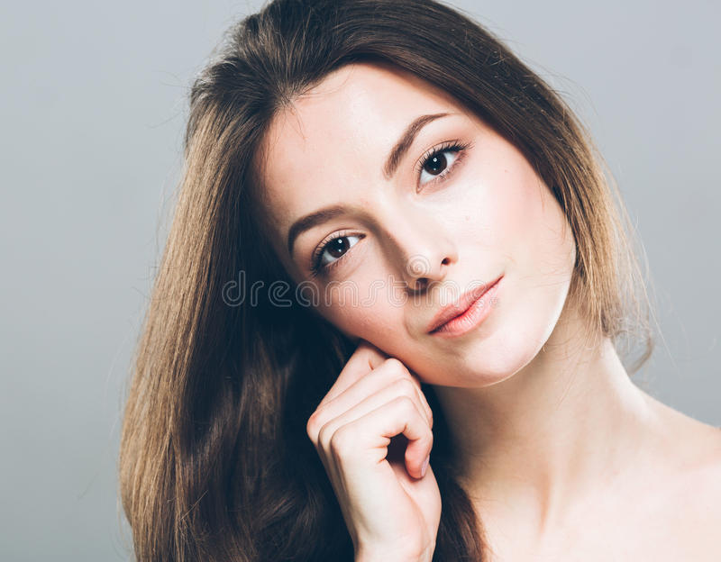 Beautiful young woman portrait cute tender pure smiling touching her ear by fingers attractive gray background royalty free stock photos