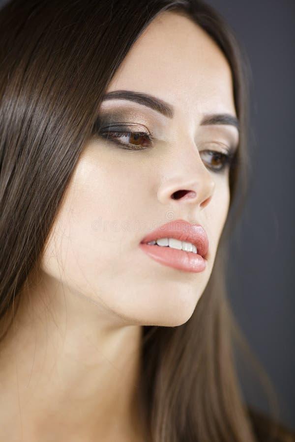 Beautiful young woman portrait. Dark background. Glamorous makeup. royalty free stock photo