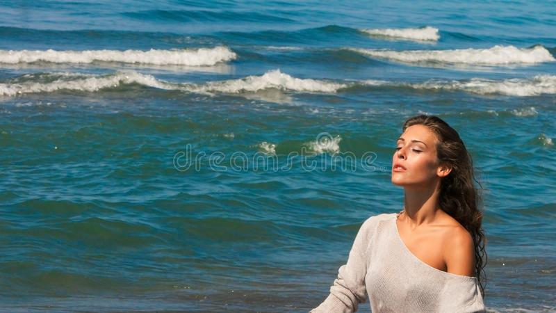 Beautiful young woman portrait enjoy in sun and sea air on beach closed eyes relaxing summer. Day royalty free stock photography