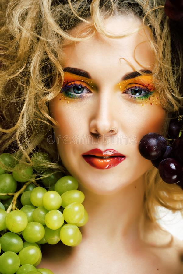 Beautiful young woman portrait excited smile with fantasy art hair makeup style, fashion girl with creative food fruit. Orange, grapes, citrus make up, happy royalty free stock photo