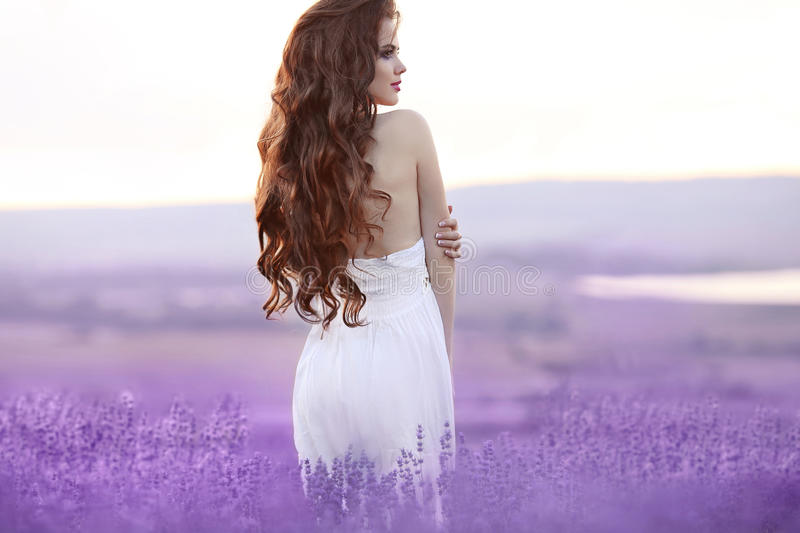 Beautiful young woman portrait in lavender field. Attractive brunette girl with long curly hair style in white dress dreaming. royalty free stock images