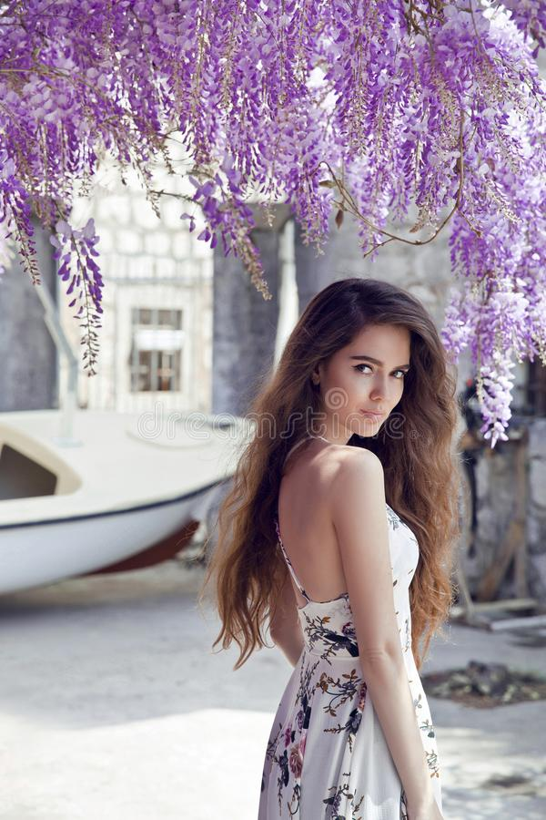 Beautiful young woman portrait over wisteria blossom. Attractive royalty free stock images