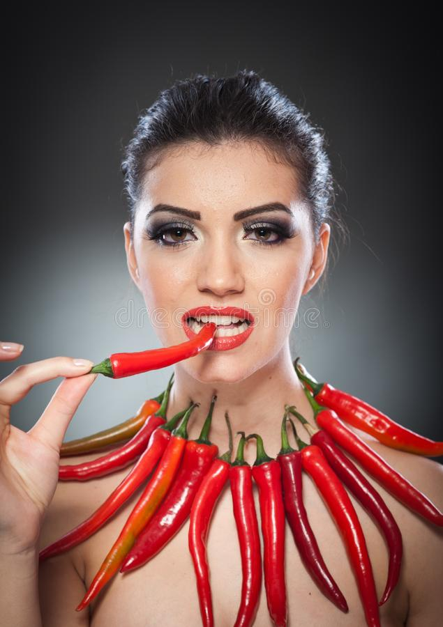 Beautiful young woman portrait with red hot and spicy peppers, fashion model with creative food vegetable make up. Looking side to empty copy space, over black stock images