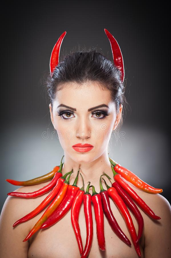 Beautiful young woman portrait with red hot and spicy peppers, fashion model with creative food vegetable make up. Looking side to empty copy space, over black royalty free stock image