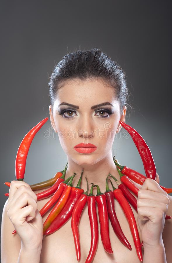 Beautiful young woman portrait with red hot and spicy peppers, fashion model with creative food vegetable make up. Looking side to empty copy space, over black stock image
