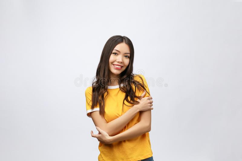 Beautiful young woman portrait. Smiling asian lifestyle concept with crossed arms. Isolated on grey background stock photo