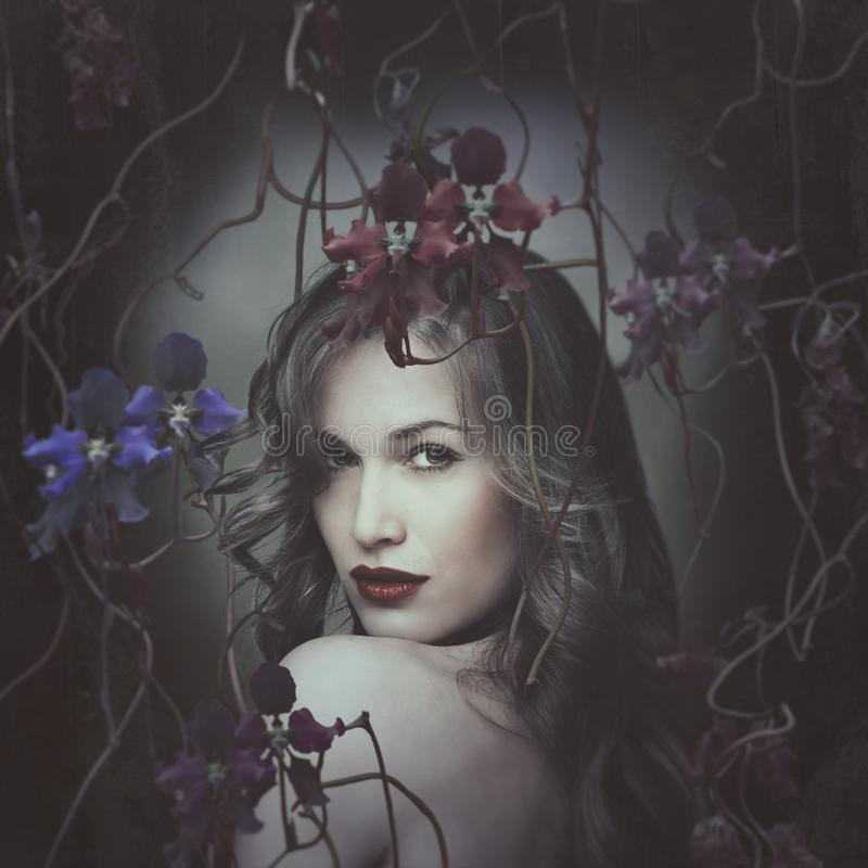 Beautiful young woman portrait surrounded by orchids royalty free stock photography