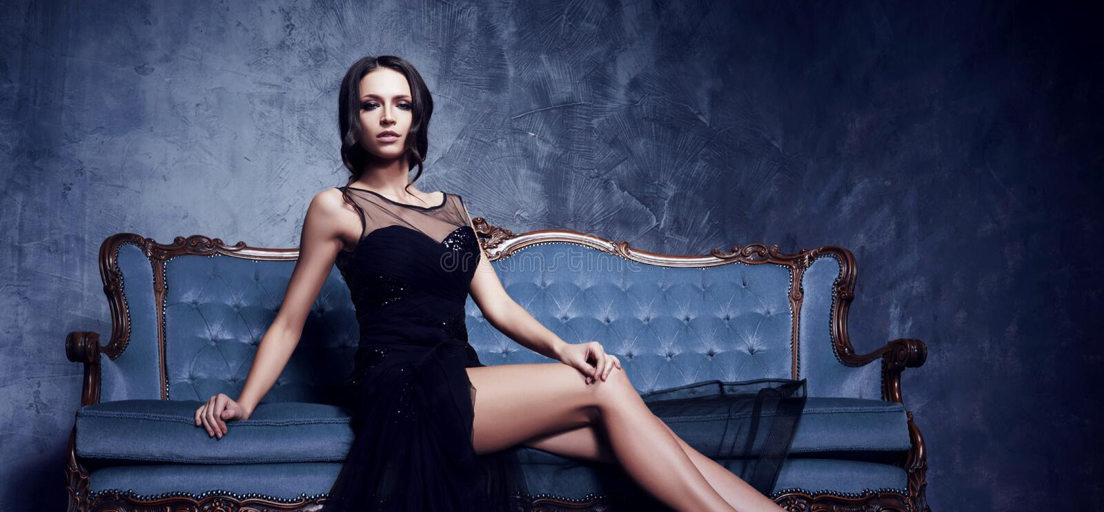 Beautiful and young woman posing in black dress on blue sofa. Vi stock photo