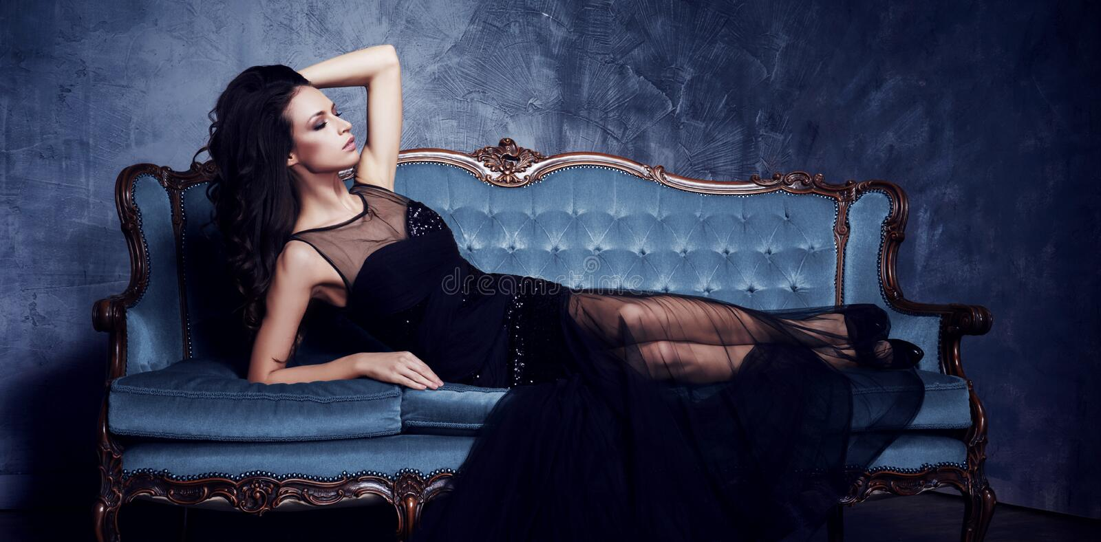 Beautiful and young woman posing in black dress on blue sofa. Vi. Ntage interior and retro background royalty free stock images