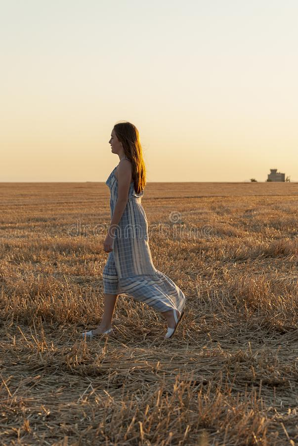 Beautiful young woman posing in a field wearing a blue and white dress, at sunset on a summer day. Red-haired. Teenager stock photos