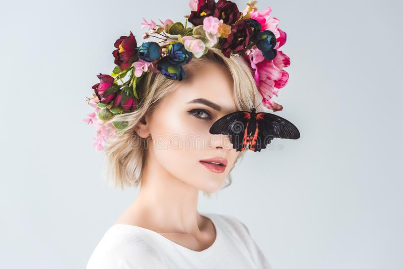 beautiful young woman posing in floral wreath with butterfly, stock images
