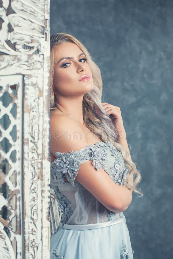 Beautiful young woman posing luxurious interior. Vintage romantic portrait of blonde girl royalty free stock images
