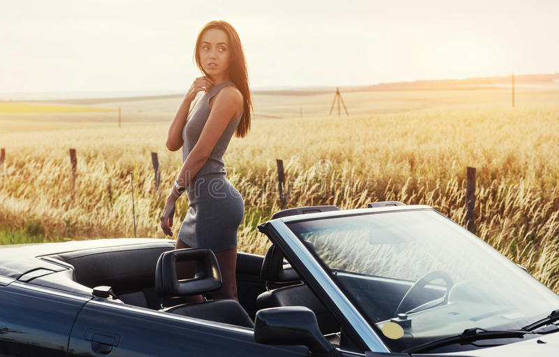 Beautiful young woman posing near a car on the road royalty free stock photo