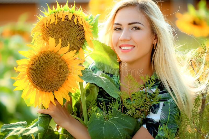 Beautiful young woman posing near sun flowers. summer portrait at the field. Happy woman in beauty field with sunflowers stock images