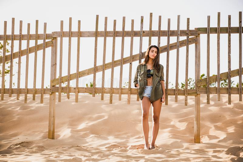 Beautiful young woman posing near a wood fence royalty free stock photography