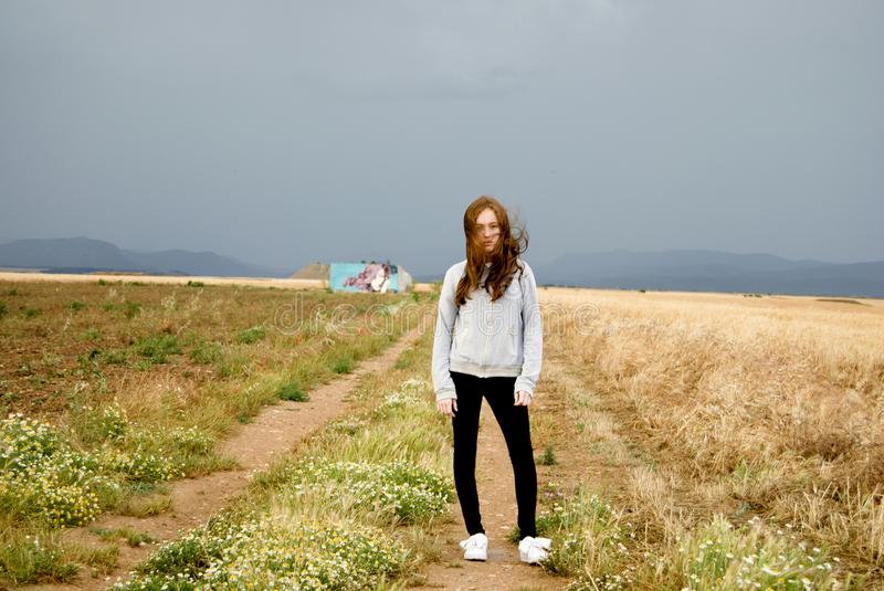 Beautiful young woman posing in a path between two wheat fields. cloudy day. Red-haired. Teenager royalty free stock photo