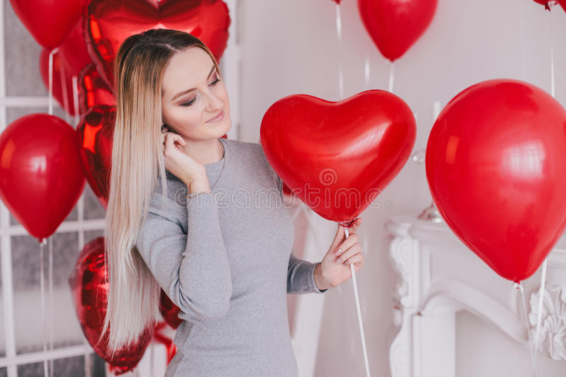 Beautiful young woman posing with red heart balloons in a white room stock images