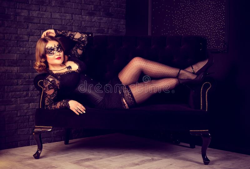 Beautiful young woman posing in stockings and Venetian mask on sofa. Retro glamor vintage woman. Carnival Masquerade women stock image