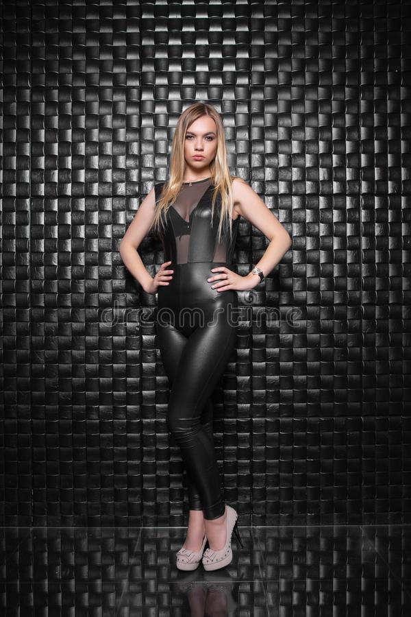 Beautiful young woman. Posing in the studio, dressed in a black leather suit royalty free stock image