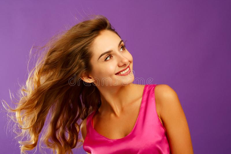 Beautiful young woman posing in studio over violet background. F royalty free stock photos