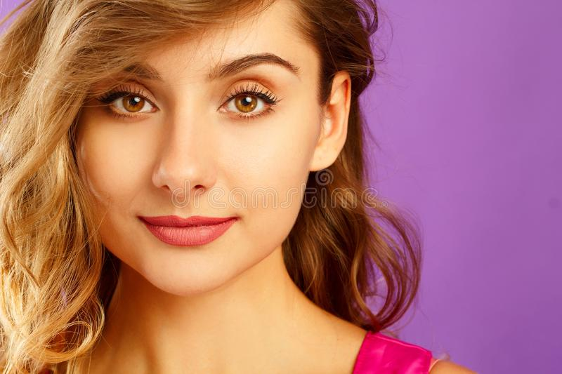 Beautiful young woman posing in studio over violet background. F stock image