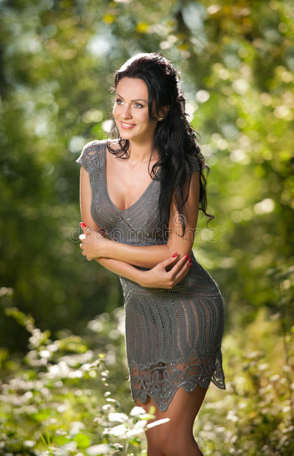 Beautiful young woman posing in a summer meadow. Portrait of attractive brunette girl with long hair relaxing in nature, outdoor. Shot in sunny day. Lady in royalty free stock photos