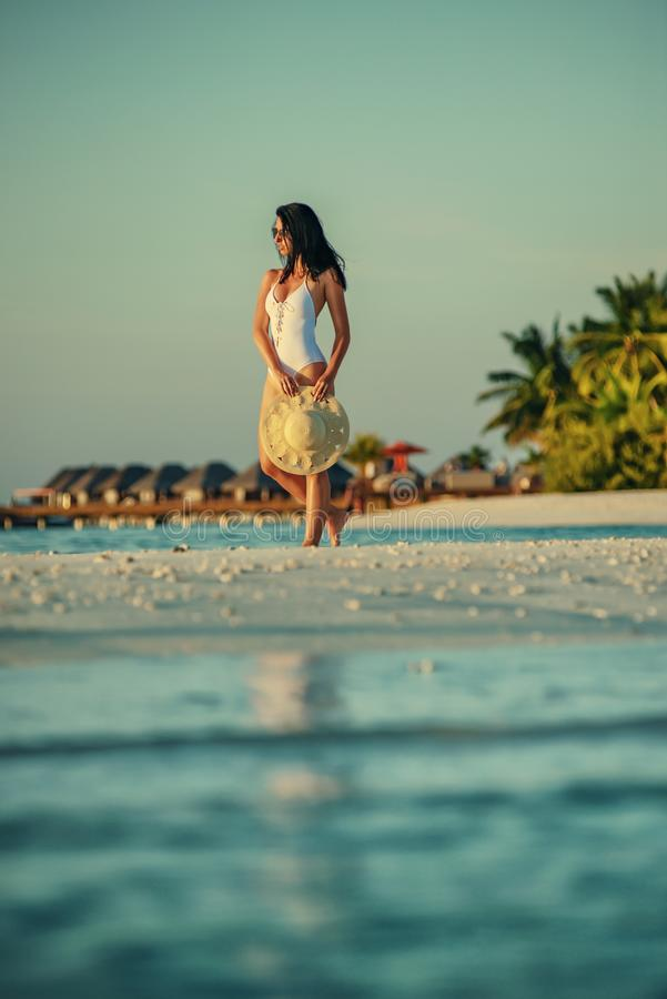 Beautiful young woman posing on white beach, beautiful scenery with woman in maldives, tropical paradise royalty free stock images