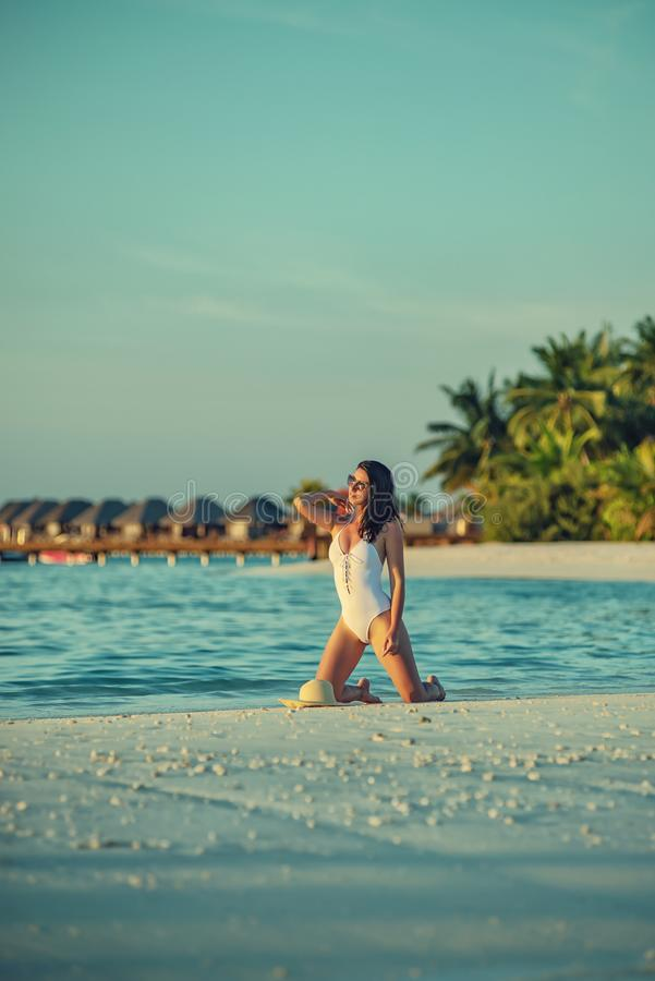 Beautiful young woman posing on white beach, beautiful scenery with woman in maldives, tropical paradise royalty free stock photos