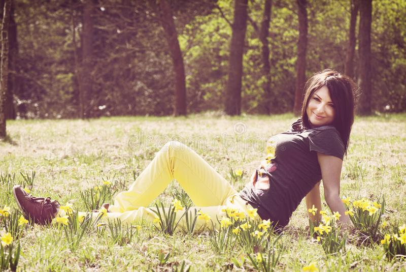 Beautiful young woman posing with yellow daffodils on the meadow stock photography